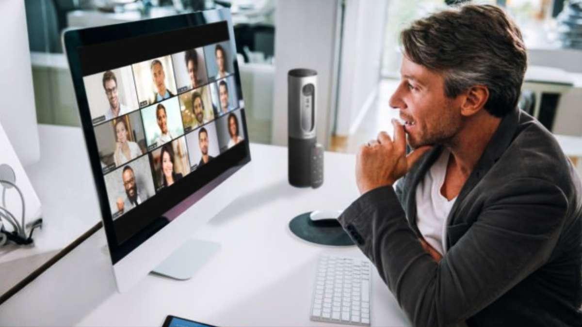 Hombre frente al ordenador en que se ven varias personas en videoconferencia. Momento de cuidar a los trabajadores